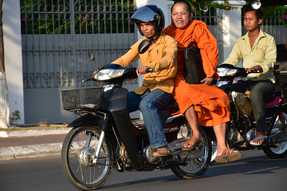 Nebbish Buddhist Monk at the Back of Motorbike 2