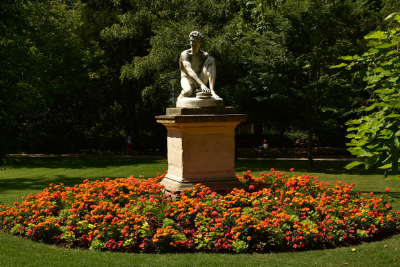Statue of Nude Man in Bed of Orange and Red Flowers 2