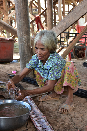 Elderly Woman Cleaning Fish