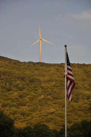 Wind Turbine on Tree-Covered Hill with American Flag
